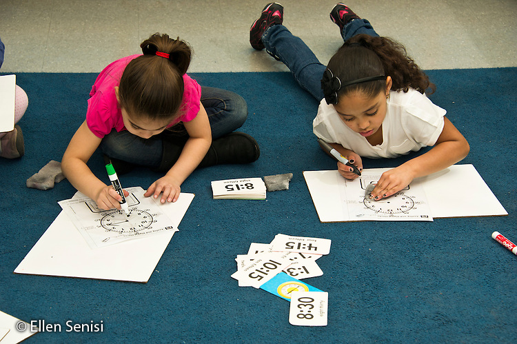 MR / Schenectady, New York. Paige Elementary School (urban public elementary school). First grade independent work at learning center time. Students (girls: 7) work side by side on their time telling skills using dry erase board. MR: Dei1, Liv3. ID: AL-g1g. © Ellen B. Senisi.