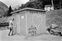 """Switzerland. Canton Ticino. Maggia valley. Cevio. A man working for Cevio's village opens the door of a small building intended for electricity purpose. A heart is painted on the wall with the words """"Tourist""""and """" Hyper"""". 12.05.2015 © 2015 Didier Ruef"""