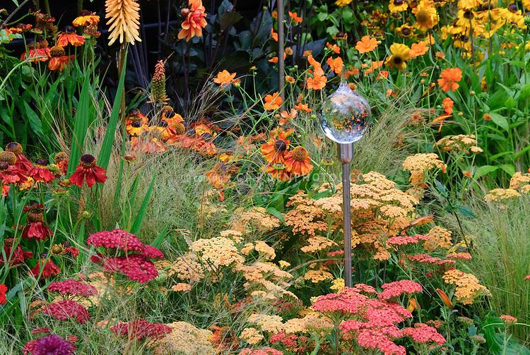 Achilea, Helenium, Kniphofia, Dahlia, ornamental grass, glass garden ornament for sunset hot warm toned color theme garden of orange, yellow, reds perennials flowers, glass flower