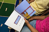 MR / Schenectady, NY. Zoller Elementary School (urban public school). Kindergarten classroom. Two bilingual students, both who are native Spanish speakers, read Spanish-language book about shapes. Book is entitled Las formas donda jugamos (Shapes Where We Play) by Ellen Senisi. MR: AM-gKw. ID: AM-gKw. © Ellen B. Senisi.