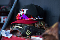 A Hickory Crawdads cap sits on top of a glove in the home dugout during the game against the Savannah Sand Gnats at L.P. Frans Stadium on June 15, 2015 in Hickory, North Carolina.  The Crawdads defeated the Sand Gnats 4-1.  (Brian Westerholt/Four Seam Images)