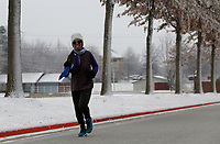 Tangel (cq) Clinard jogs Thursday, February 11, 2021, the snow and tree lined Cypress Point Drive in Springdale. Clinard is training to pace the 4:45 group of the Hogeye Marathon that will take place Saturday, April 24th starting and ending in downtown Springdale. Information about the race can be found at hogeyemarathon.com. Check out nwaonline.com/210212Daily/ and nwadg.com/photos for a photo gallery.<br /> (NWA Democrat-Gazette/David Gottschalk)