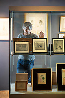 BNPS.co.uk (01202) 558833. <br /> Pic: CorinMesser/BNPS<br /> <br /> Pictured: Museum Director Adrian Green in the new exhibition<br /> <br /> Original artwork from the acclaimed James Bond illustrator has gone on display at a new exhibition.<br /> <br /> Richard Chopping produced the drawings for nine of the 007 book covers from 1957 to 1966.<br /> <br /> Examples of his craft, including his striking skull design for Goldfinger, are being showcased at Salisbury Museum in Wiltshire.