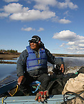 Experienced Vuntut Gwitchin First Nation hunter and trapper, Joel Peter, enjoys a cigarette as he keeps watch for the Porcupine caribou to cross the Porcupine River near Old Crow, Yukon Territory, Canada.
