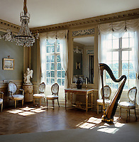 This ante-room is furnished with delicately carved chairs covered in floral chintz, the wall panels are painted Wedgewood blue and a replica of Sergel's Cupid and Psyche stands in the corner