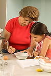 8 year old girl at home cooking baking with grandmother