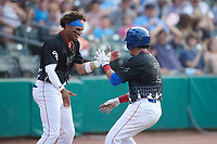 Carlos Sepulveda (27) of the Tennessee Smokies celebrates with teammate Brennen Davis (left) after hitting a home run during the game against the Chattanooga Lookouts at Smokies Stadium on July 31, 2021, in Kodak, Tennessee. (Brian Westerholt/Four Seam Images)