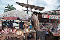 Nigeria. Enugu State. Enugu. Street shops. Meat market. A pig has been slaughtered by two butchers, The dead animal's raw meat is laid on a wooden stall. A black woman sells lottery tickets, films on compact disks (CD) and various magazines ( war, fight, martial arts, animals,…). Two solar panels fixed on poles. Both are out of order. 10.07.19 © 2019 Didier Ruef