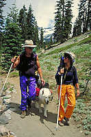 couple on wilderness trail hiking with dog. couple. California USA.