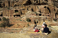 Bedouin children sitting on a rock outside the entrance to the Royal Tombs carved into the cliffs at Petra, Jordan.