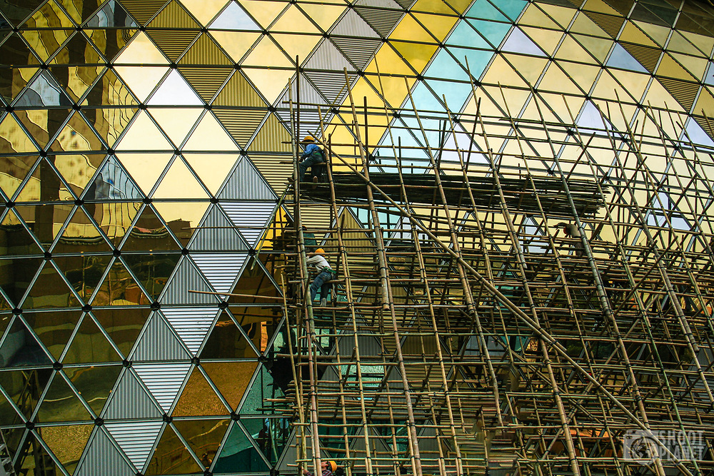 2006 construction of the iconic Grand Lisboa casino, with workers on bamboo scaffolding  adjusting the modern, golden windows, in Macao China