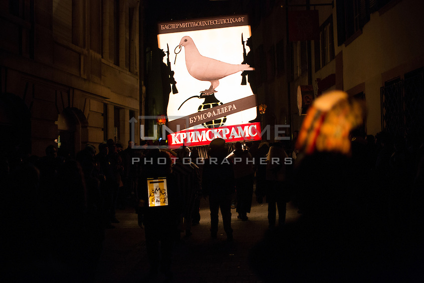 A lantern with a dove perched on top of a grenade is carried during 'Morgenstreich', when about 200 lanterns are carried by 'cliques' through a completely dark old town of Basel, moments after the start of the 2015 Fasnacht, Carnival of Basel in Switzerland. Feb. 23, 2015.