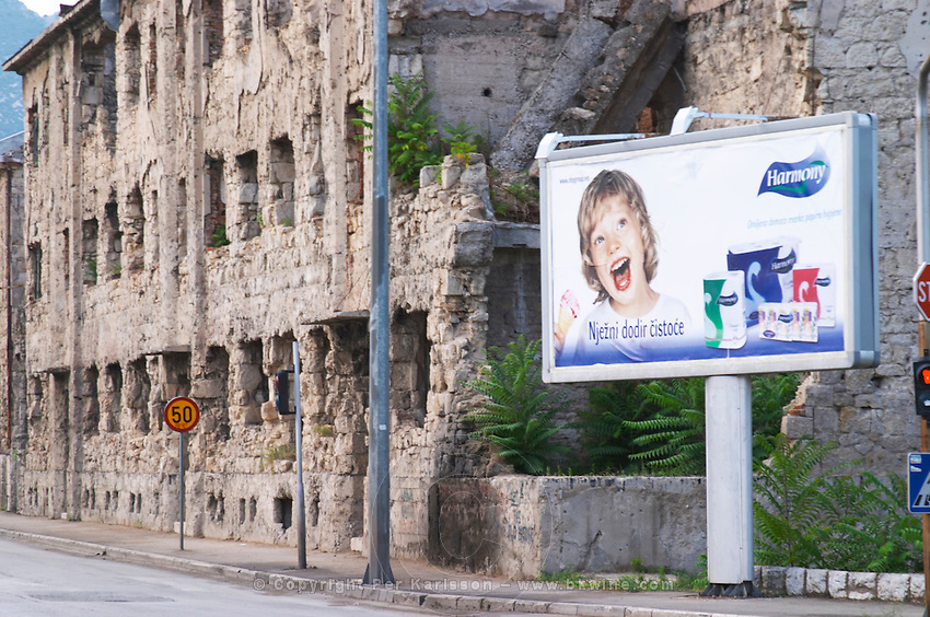 Building in Mostar damaged by the war and still not renovated. Ruined by bullet holes, mortar bomb shell grenade damage, very close to the beautifully renovated old town city centre. A bizarre contrast with a bill board advertisement saying 'Harmony' publicity for tissue and toilet paper and showing a happy young child eating ice-cream. Town of Mostar. Federation Bosne i Hercegovine. Bosnia Herzegovina, Europe.