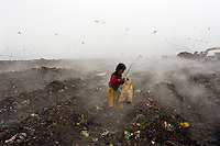 7 year old Jasmine collects rubbish from a steaming rubbish tip on a cold winter morning.  She earns money to support her family by scavenging for items on the Kajla rubbish dump.  It is one of three landfill sites in this city of twelve million people.  Around 5,000 tonnes of garbage are dumped here each day and over a thousand people work among the rubbish, sorting through the waste and collecting items to sell to retailers for recycling.