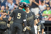 Vanderbilt Commodores catcher Phillip Clarke (5) celebrates with teammate Pat DeMarco (18) after his seventh inning home run against the Michigan Wolverines during Game 2 of the NCAA College World Series Finals on June 25, 2019 at TD Ameritrade Park in Omaha, Nebraska. Vanderbilt defeated Michigan 4-1. (Andrew Woolley/Four Seam Images)