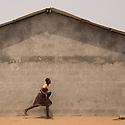 Ghana - Fuveme - A schoolgirl runs for cover as the ocean waves start flooding the village.