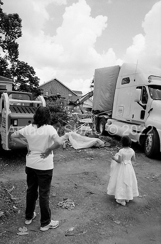 Saint Bernard's Parish, Louisiana.May 27, 2006..Linda Manalla, in her 60s, and her neighbor Reagan Cavignal 7 years old, who just made her first communion come to watch their home for 35 years be torn down after it was moved off its foundation by hurricane Katrina. She and her husband raised 3 girls in their house and Linda's parents lived just across the street until they died last year a few months before Katrina hit...They have since purchased a home in Slidell. ..FEMA funded demolition teams work at leveling 6000+ homes in St. Bernard's Parish damaged by hurricane Katrina in August of 2005...FEMA is offering to destroy homes for free up until June 30, 2006. About 12 homes are being demolished daily.