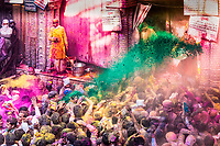 Holi at Banke Bihary Temple, believed birthplace of Krishna, with priest throwing colored green water on devotees, in Vrindavan, Uttar Pradesh, India