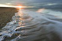 Coastal landscape of waves washing upon the sandy beach along Norton Sound, Bering Sea, Nome, in western arctic Alaska.