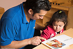 Education Preschool 2-3 year olds sad girl listening to father read book at start of day