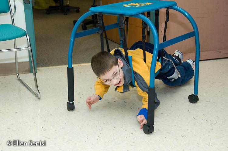 MR / Albany, NY.Langan School at Center for Disability Services .Ungraded private school which serves individuals with multiple disabilities.Child uses a belly crawler as he crawls down the hall. Student is weaing a SWASH (sitting, walking, and standing hip apparatus) on his hips / legs). Boy: 9, cerebral palsy, limited verbal output with expressive and receptive language delays.MR: Rub1.© Ellen B. Senisi