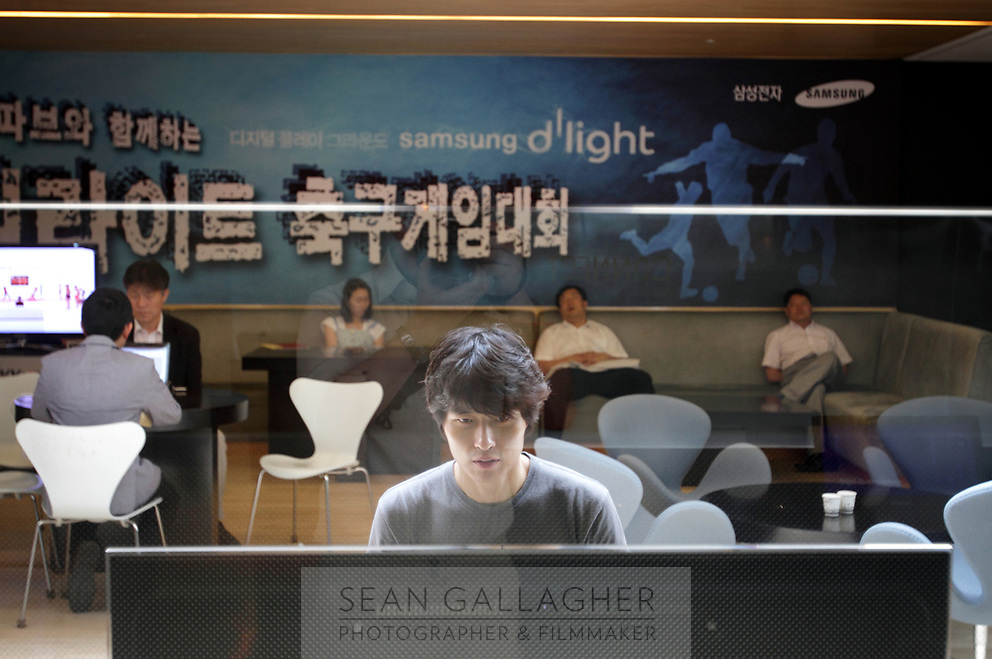 SOUTH KOREA. A man plays video games inside the main showroom of Samsung, at their head-office in downtown Seoul. 2010
