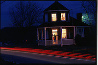 A shadowy figure stands in the door where wagons lined up 20 deep at Searights Tollhouse.  It is one of six built in Pennsylvania when the U.S. turned the road--and its expense--over to the state in the mid-1830s. Designed by the Army Corps of Engineers, the buildings resemble lighthouses. Traffic streams the historic building at dusk.