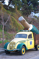 Cave Guinot. Yellow and Green old Peugeot 202 car with a gigantic Limoux bottle serving as an advertisement publicity for the winery. Limoux. Languedoc. France. Europe.