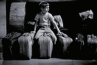 YOUNG BOY SITS ON FAMILY SUITCASES, WAITING FOR TRAIN, TRAVEL, COMMUTING, TRANSPORTATION, CHILD, ESSAY AVAILABLE, LIGHT STUDY. PHILADELPHIA PA.
