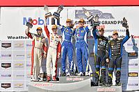 #81 BimmerWorld Racing, BMW 328i, ST: Nick Galante, Devin Jones celebrates the win on the podium #37 MINI JCW Team, MINI JCW, ST: Derek Jones, Nate Norenberg, #21 Bodymotion Racing, Porsche Cayman, ST: Max Faulkner, Jason Rabe