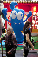 China. Shanghai. World Expo. Expo 2010 Shanghai China.  China Pavilion. Two chinese tourists, an old woman and a mature lady, stand and pose for a picture in front of Haibao, which is the name of the mascot of World Expo 2010 Shanghai China. Hai Bao means the treasure of the sea. The name of Hai Bao is easy to remember, echoes with the color of its body and is a typical lucky name in Chinese tradition. Hai Bao is the good well ambassador of Shanghai Expo and is embracing friends from all over the world with his arms and confident smile.  25.06.10 © 2010 Didier Ruef