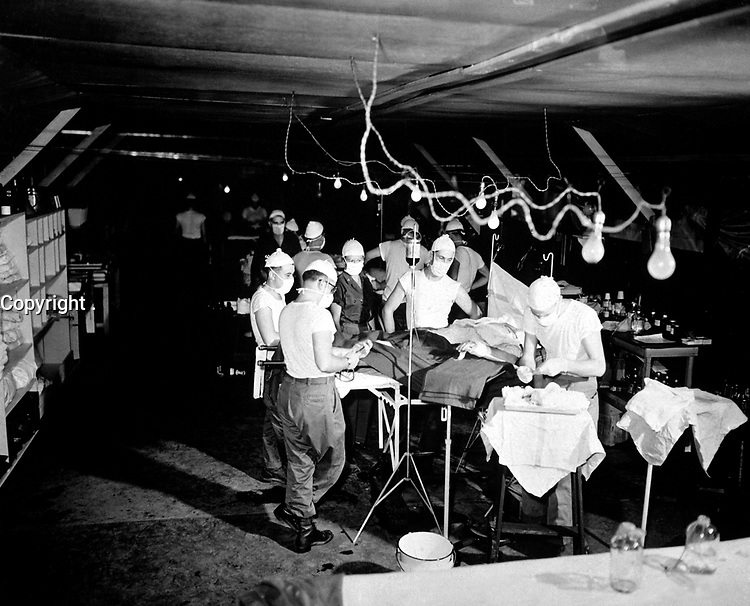 An operation is performed on a wounded soldier at the 8209th Mobile Army Surgical Hospital, twenty miles from the front lines.  August 4, 1952.  Feldman.  (Army)<br /> NARA FILE #  080-SC-409689<br /> WAR & CONFLICT BOOK #:  1458