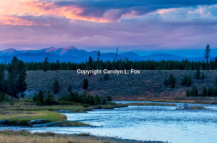 The sun set over the mountains at Barnes Hole in Yellowstone National Park.