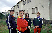 """Teenagers pass the time outside boarded up and empty houses on an estate in Distington, Cumbria which suffers from """"low demand"""" as a result of high local unemployment."""