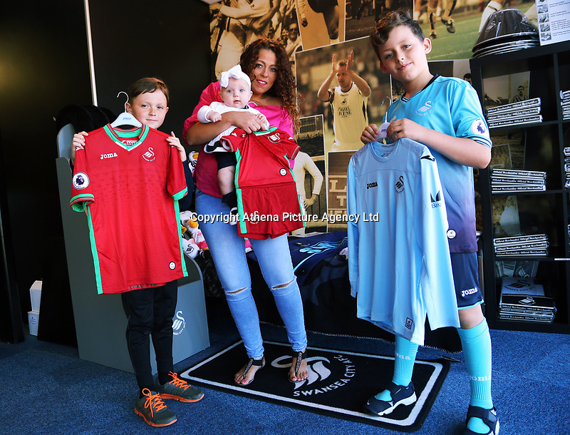 Pictured L-R: Jack Lewis, 9, Maria Thomas holding Annabelle, 5 months and Bailey Dyer, 10. Saturday 01 July 2017<br /> Re: The new 2017-2018 season, Swansea City FC kit has officially gone on sale at the club's Liberty Stadium shop, Wales, UK