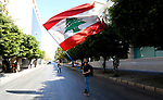 Lebanese protester holds a Lebanese flag, as he walks on a blocked main road that leads to the Central Bank during a protest against the increase in prices of consumer goods and the crash of the local currency, in Beirut, Lebanon, March 16, 2021. Scattered protests broke out on Tuesday in different parts of the country after the Lebanese pound hit a new record low against the dollar on the black market. Photo by Marwan Bou Haidar