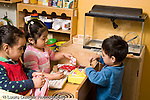 Educaton preschool  3-4 year olds two girls and a boy pretend play in kitchen family area interacting horizontal