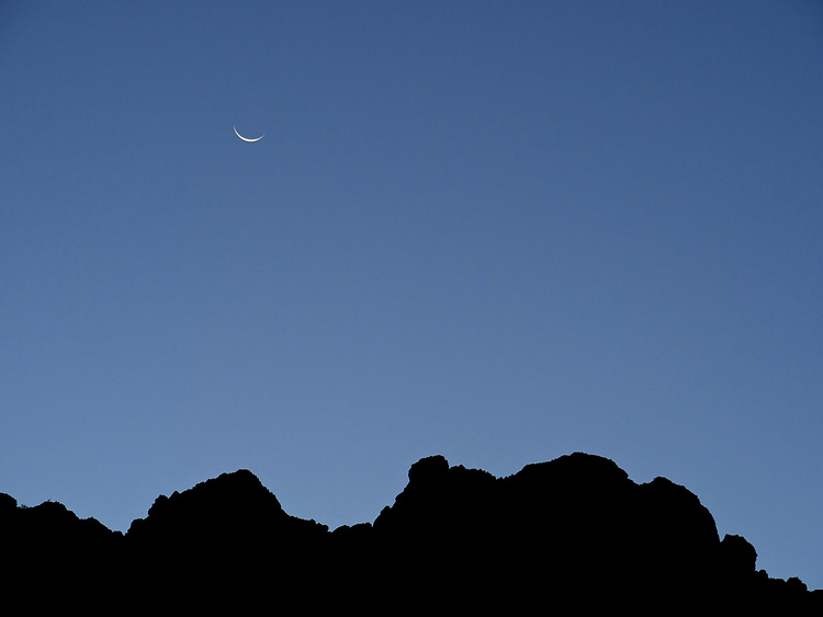 A crescent moon rises over the cliffs before sunrise in the Grand Canyon, Grand Canyon National Park, Arizona, USA