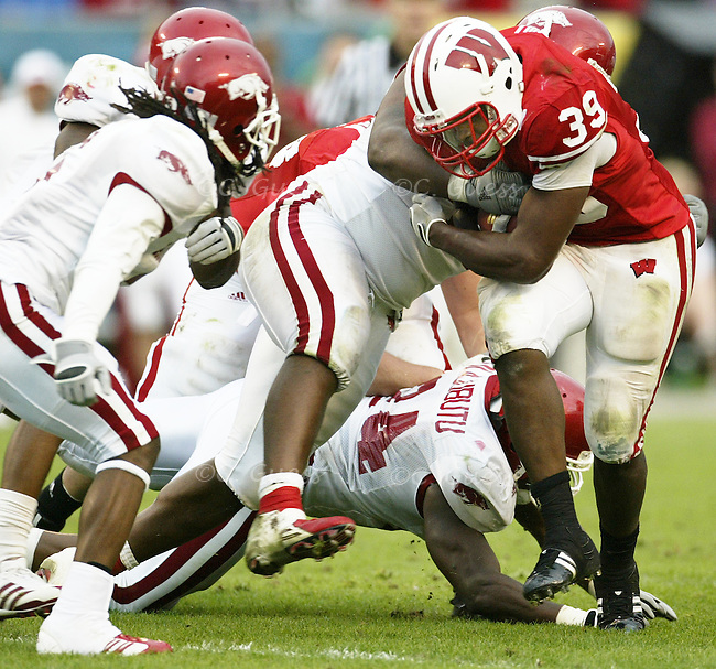 Running back P.J. Hill evades a tackle by numerous Arkansas players on an offensive drive.<br />