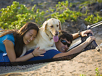 Young local Hawaii family playing in hammock with their dog
