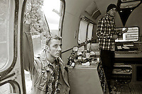 "Musicians listening to a recording just made.  An airstream trailer fitted out as a mobile sound recording engineer's mixing base .  Set up to record the ""Edge of Chaos Orchestra"" playing inside the Blue Coconut Club, Pulborough, West Sussex."