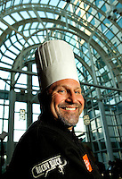 Event photography of Charlotte's Taste of the Nation 2012 event, a fundraiser and awareness event for childhood hunger. Created by Share our Strength, Taste of the Nation brings together culinary creatives and thousands of volunteers annually. The Charlotte event takes place each April in the Wells Fargo atrium in Center City Charlotte. Photo shows executive chef David Bettendorf of Rocky River Grille, located in the Concord NC Embassy Suites.