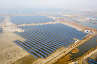 A solar farm sits under a blanket of smog in the Hanggu region of Tianjin. Land subsidence has been a problem in the region and exacerbates the risk of flooding from rising sea levels and storm surges. Solar farms and other energy generating industries are located in this region and will be some of the first to be impacted as sea levels rise and storm surges increase. 2019