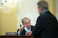 United States Senator Lindsey Graham (Republican of South Carolina) speaks to United States Senator David Perdue (Republican of Georgia) during a United States Senate Committee on the Budget business meeting at the United States Capitol in Washington D.C., U.S., on Thursday, June 11, 2020, as they consider the nomination of Director, Office of Management and Budget (OMB) Russell Vought to be White House Office of Management and Budget.  Credit: Stefani Reynolds / CNP/AdMedia
