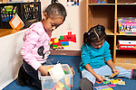 Education preschool 3-4 year olds two girls playing side by side with different toys, one building with colorful plastic bricks (Duplo), the other matching cards showing numbers and objects