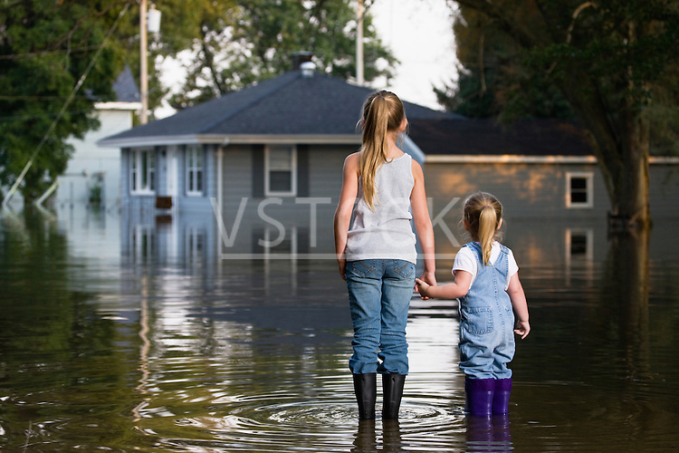 USA, Illinois, Chillicothe, Two girls (2-3, 8-9) holding hands and standing in water, rear view