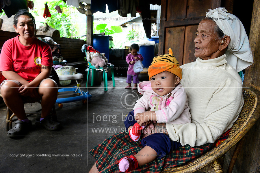 PHILIPPINES, Cordillera highlands, Bontoc, Samoki village, Igorot people, Samoki tribe, old woman take cares of her grandchildren as the parents working overseas / PHILIPPINEN, Cordilleras, Bontoc, Samuki Dorf, Igorot Volksgruppe, Samoki Clan, alte Frau Pingao Chinalpan, geb. 1936, kuemmert sich um ihre Enkel, die Eltern arbeiten im Ausland