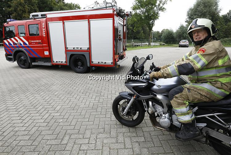 Foto: VidiPhoto<br /> <br /> LOPIK – Vrijwillig brandweerman Hans Schenkel uit Lopik woensdag in brandweeruitrusting op zijn motor voor de kazerne in Lopik. De gedreven vrijwilliger heeft inmiddels dertig reanimaties op zijn naam staan, een uitzonderlijk hoog percentage voor een vrijwilliger. Onlang kwam hij te laat voor een uitruk, maar dat weerhield hem niet om zijn collega's te hulp te schieten. Snel kleedde hij zich om en scheurde op zijn motor achter de brandweerauto aan. Het einde dreigt echter voor vrijwilligers bij de brandweer als gevolg van Europese wetgeving. Brandweervrijwilligers zoude volgens de nieuwe regels moeten worden betaald.