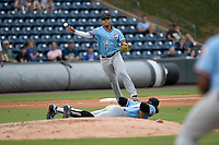 Pitcher Tyler Phillips (32) of the Hickory Crawdads lies flat on the ground to get out of the way as third baseman Tyler Ratliff (14) throws out a runner at first base during a game against the Greenville Drive on Monday, July 23, 2018, at Fluor Field at the West End in Greenville, South Carolina. Hickory won, 6-1. (Tom Priddy/Four Seam Images)