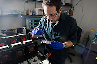Visiting graduate student Moran Neuhof (PhD student at Tel Aviv University) places planarian flatworms in an experimental apparatus in one of Michael Levin's labs in Tufts University's Center for Regenerative and Developmental Biology in Medford, Massachusetts, USA. The worms are placed in this computer-controlled automated learning and testing chamber which allows the training of flatworms in a controlled environment. Levin's research focuses on morphological and behavioral information processing in living systems. Some of the lab's recent experiments have looked at memory in flatworms using this device. A speck of food is placed in one quadrant of a petri dish and that quadrant is illuminated by a blue light. The flatworms seek out that food and retain that memory in subsequent tests even after regenerating most of their bodies.